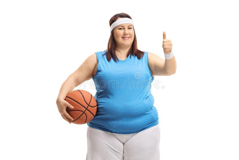 Femme de poids excessif dans les vêtements de sport tenant un basket-ball et faisant un pouce vers le haut de signe image stock