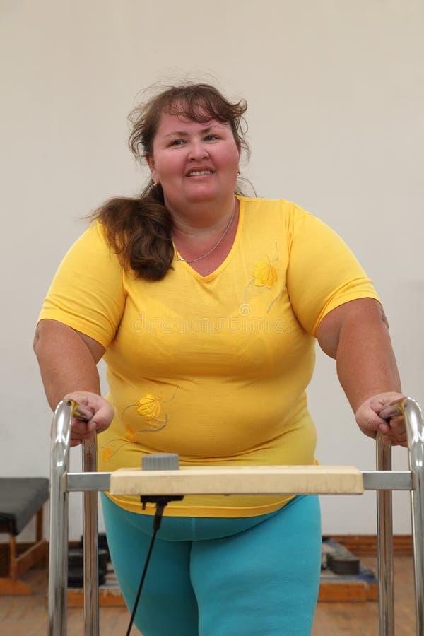Femme de poids excessif exécutant sur le tapis roulant d'avion-école photos stock