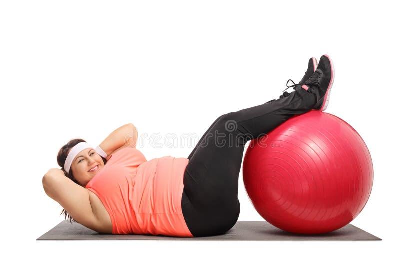 Femme de poids excessif faisant des craquements sur un tapis d'exercice images libres de droits
