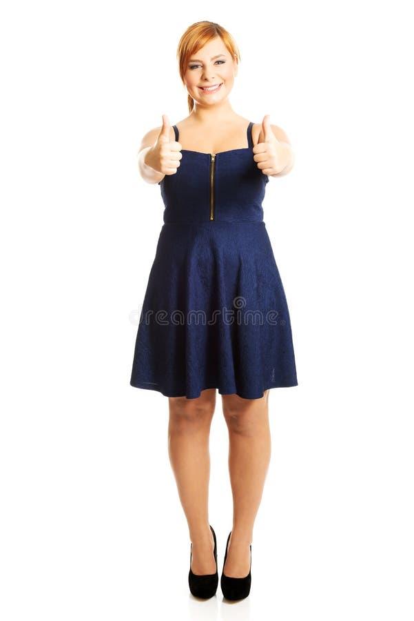 Femme de poids excessif heureuse avec des pouces  photographie stock