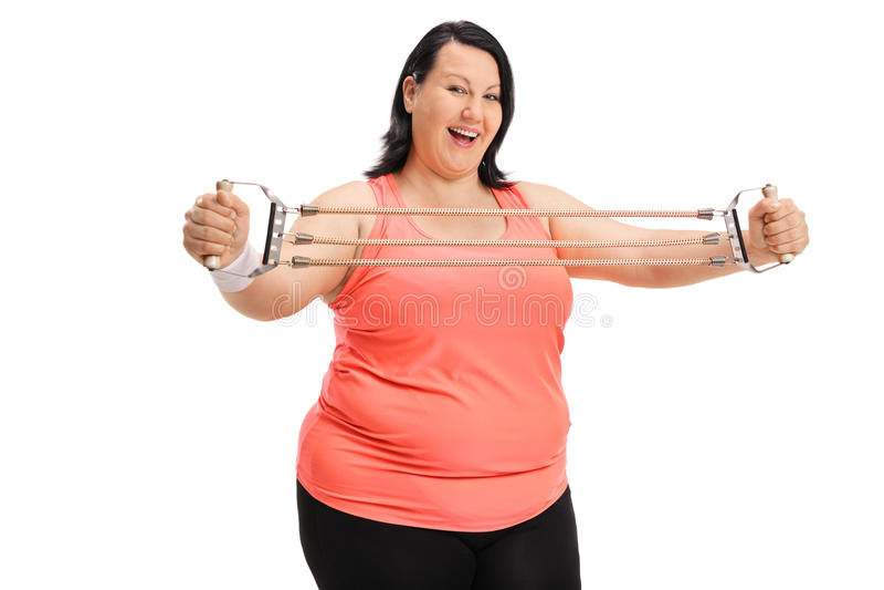 Femme de poids excessif joyeuse s'exerçant avec une bande de résistance images stock