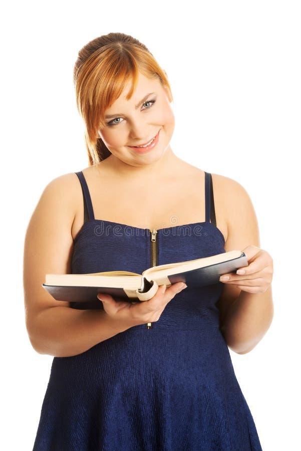 Femme de poids excessif lisant un livre photo stock