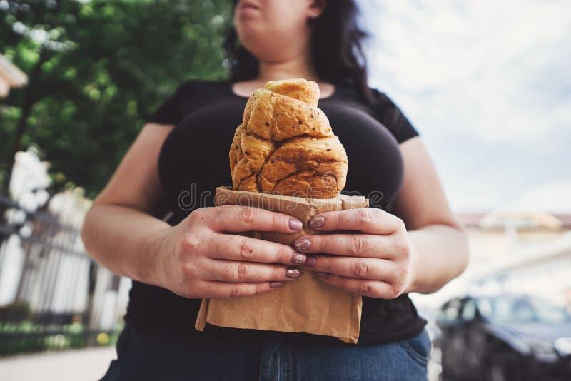 Femme de poids excessif mangeant le croissant marchant dehors image libre de droits