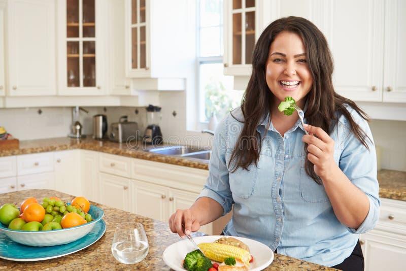 Femme de poids excessif mangeant le repas sain dans la cuisine photo libre de droits