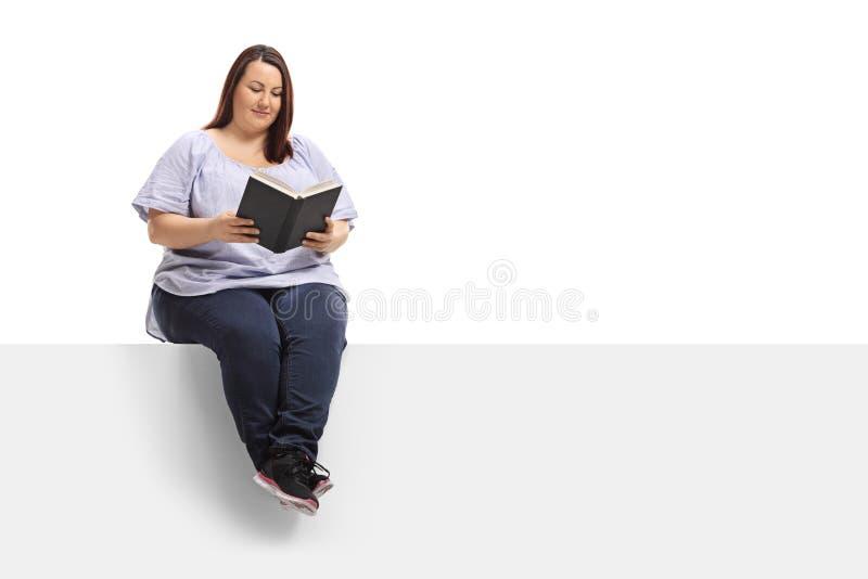 Femme de poids excessif s'asseyant sur un panneau et lisant un livre photographie stock