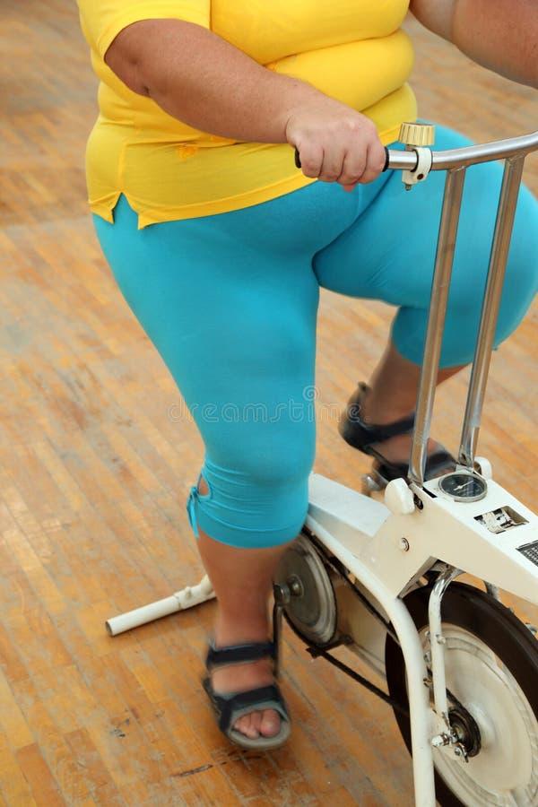 Femme de poids excessif s'exerçant sur le simulateur de vélo image libre de droits