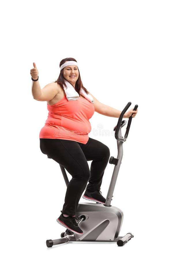 Femme de poids excessif s'exerçant sur un vélo stationnaire et faisant un Th photo stock