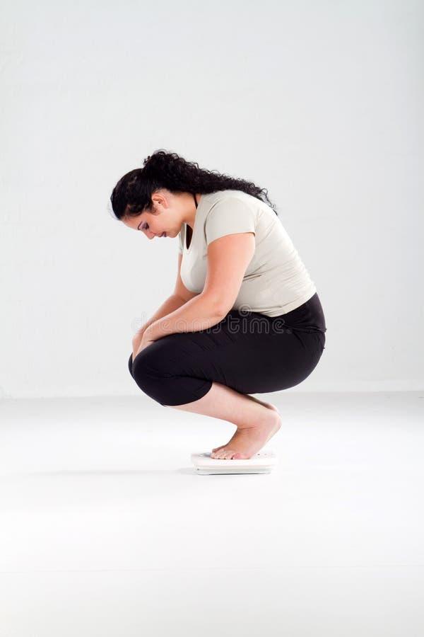 Femme de poids excessif sur l'échelle image stock