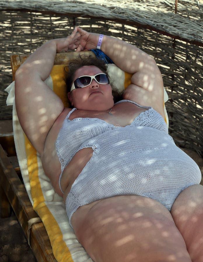 Femme de poids excessif sur la plage image stock