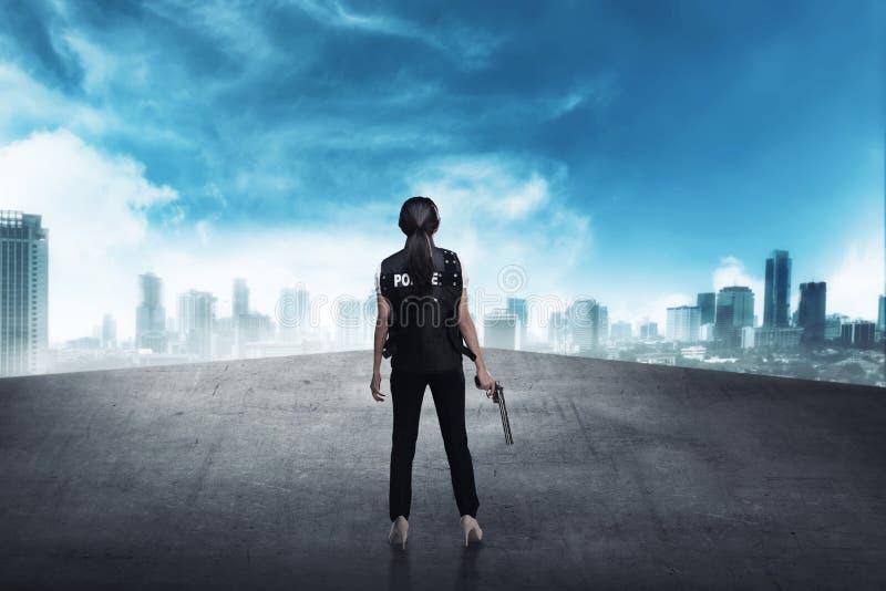 Femme de police se tenant sur le dessus de toit de bâtiment photos libres de droits