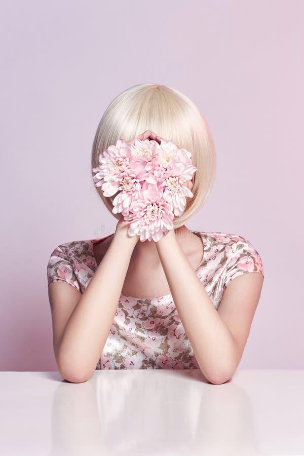 Femme de portrait d'art de mode en robe et fleurs d'été dans sa main avec un maquillage contrastant lumineux Filles créatives de  images stock