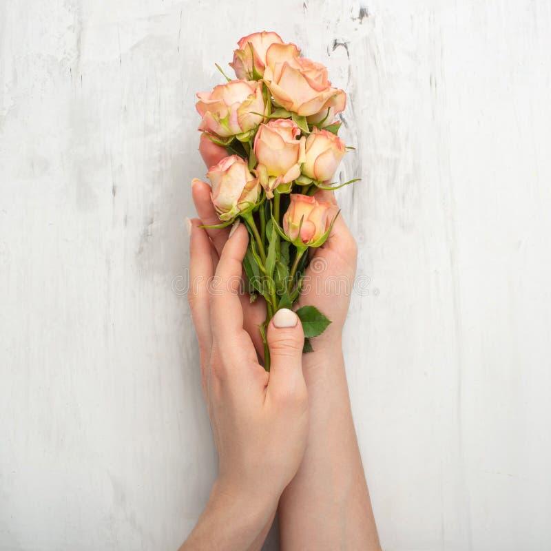 Femme de portrait d'art de mode à disposition et fleurs à disposition avec le maquillage lumineux de contraste Beauté créative d' photos libres de droits