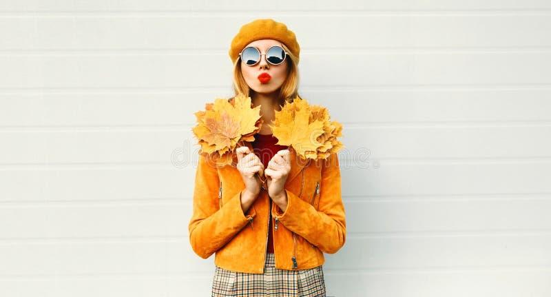 Femme de portrait d'automne tenant les feuilles jaunes d'érable soufflant les lèvres rouges envoyant le baiser doux d'air dans le photos libres de droits