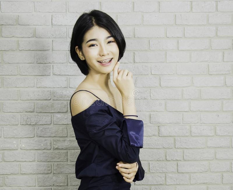 Femme de portrait d'aux cheveux courts noir dans la robe bleue luxueuse, fond de mur de briques avec le concept lumineux et migno images libres de droits