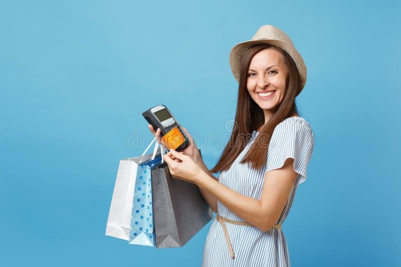 Femme de portrait dans la robe, chapeau tenant des sacs de paquets avec des achats après achats, terminal moderne sans fil de pai image libre de droits