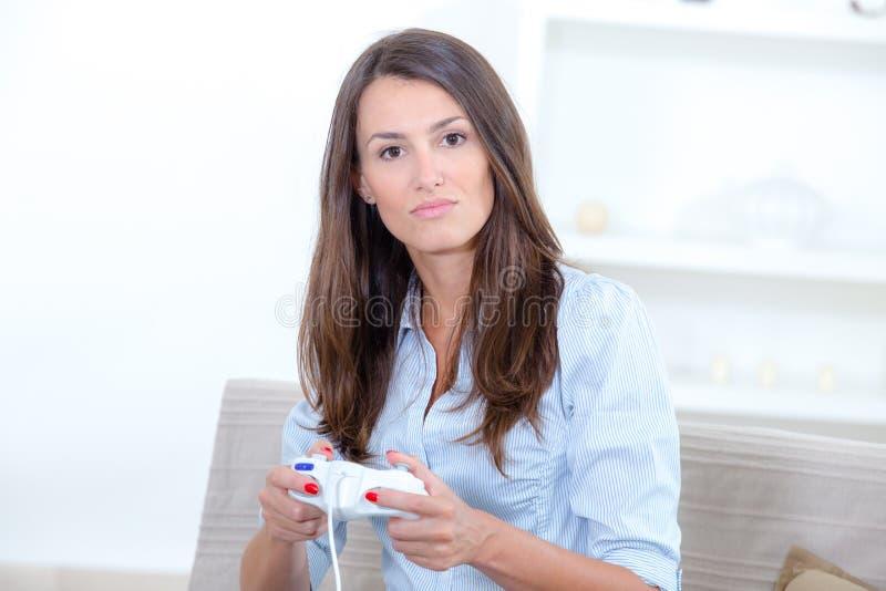 Femme de portrait jouant des jeux vidéo sur le fond gris photographie stock