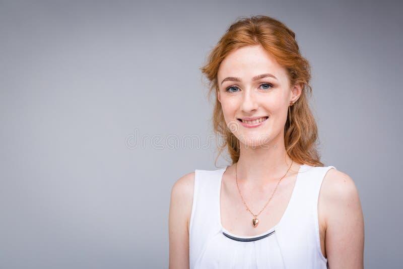 Femme de portrait de plan rapproché jeune, belle d'affaires, étudiante avec les cheveux lred et bouclés et les taches de rousseur photos stock