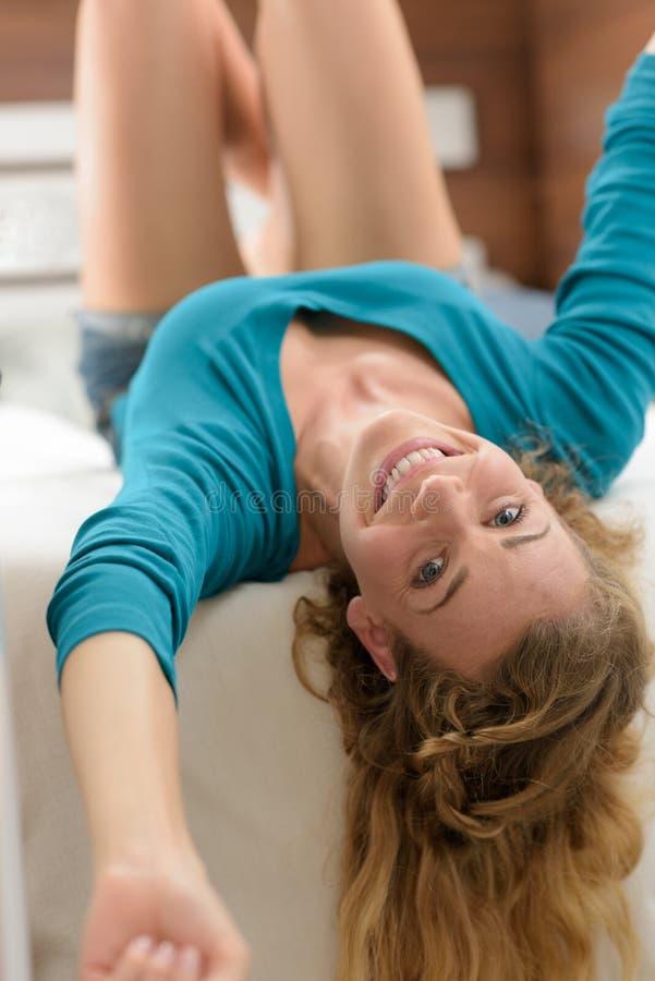 Femme de portrait s'étendant sur le lit photographie stock libre de droits
