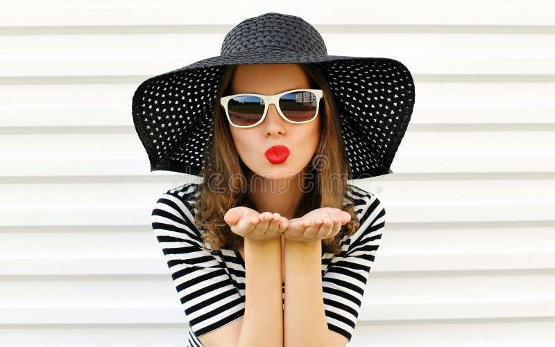 Femme de portrait soufflant les lèvres rouges envoyant le baiser doux d'air dans le chapeau de paille noir d'été sur le mur blanc photos stock