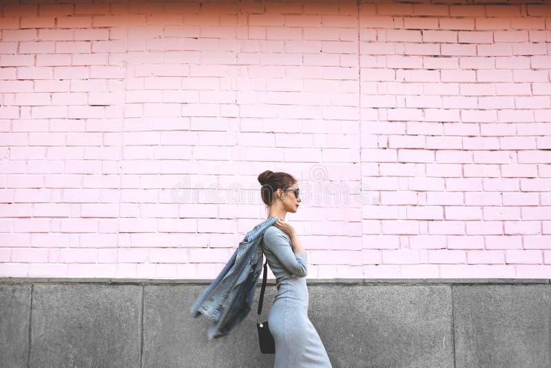 Femme de pousse de style de rue sur le mur rose Veste de port de jeans de fille de butin, robe grise, Sunglass Mode de vie de mod photos libres de droits