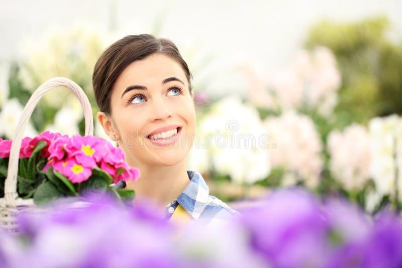 Femme de printemps souriant dans le jardin et recherchant avec wic blanc image stock