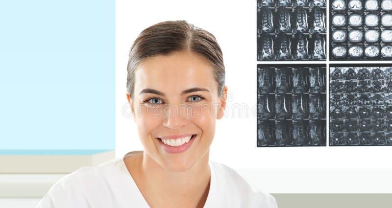 Femme de radiologue souriant avec le rayon X à l'arrière-plan photos stock