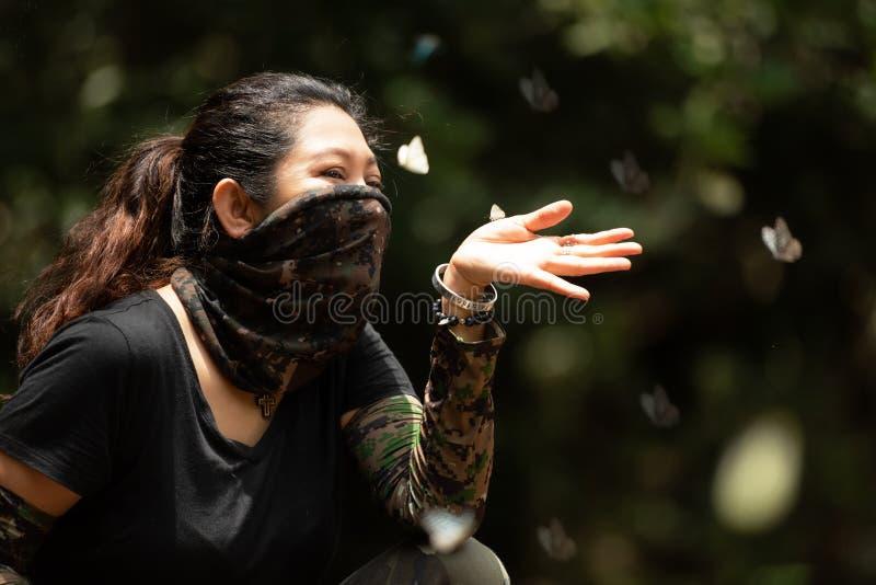 Femme de randonneur jouant avec un papillon photographie stock libre de droits
