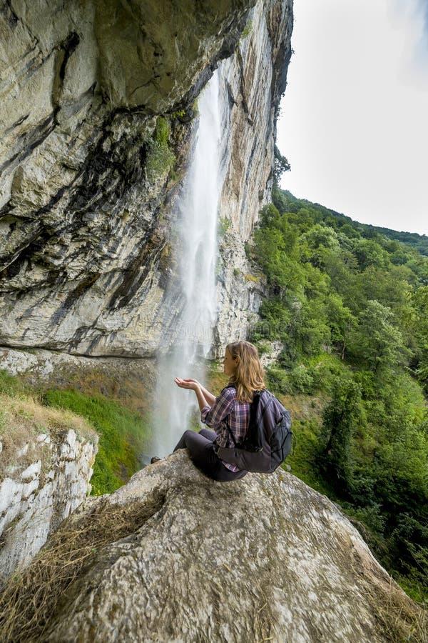 Femme de randonneur s'asseyant sur une roche avec le sac à dos tout en admirant le s image libre de droits