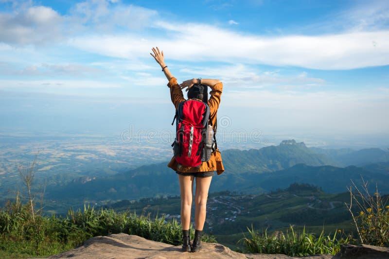 Femme de randonneur sentant le revêtement victorieux sur la montagne, photo stock