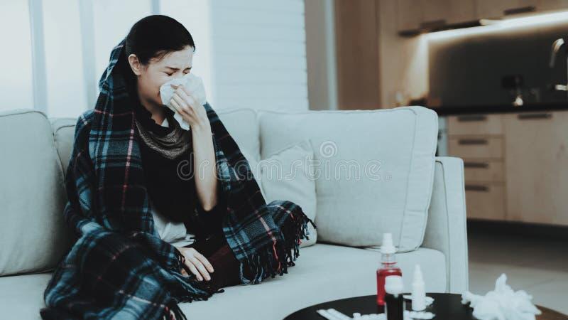 Femme de renversement avec le froid sur le sofa dans l'écharpe à la maison Jeune femme malade Sofa blanc dans la chambre Femme ma images stock