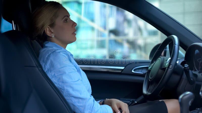 Femme de renversement fatiguée après jour ouvrable, se reposant dans la voiture, pensant au-dessus des problèmes image stock
