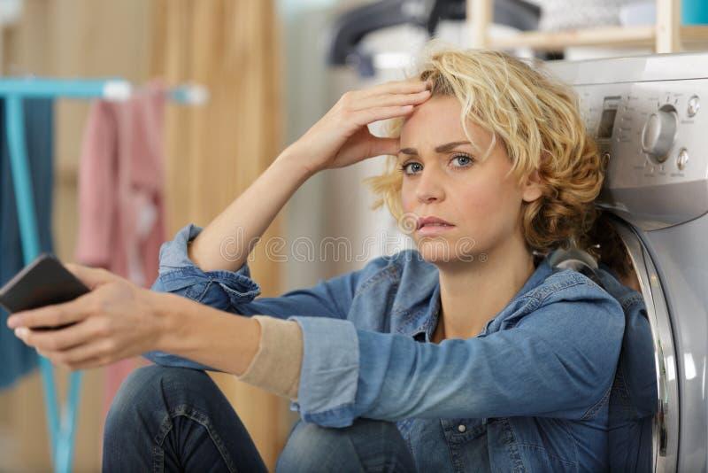 Femme de renversement posant à côté de la machine à laver photos stock