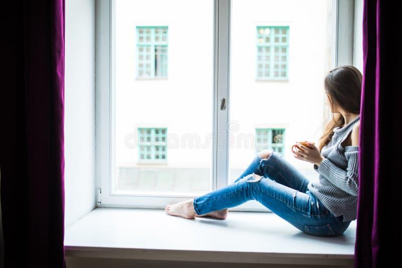 Femme de repos et de pensée Fille calme avec la tasse de thé ou de café se reposant et buvant sur le fenêtre-filon-couche à la ma photos libres de droits