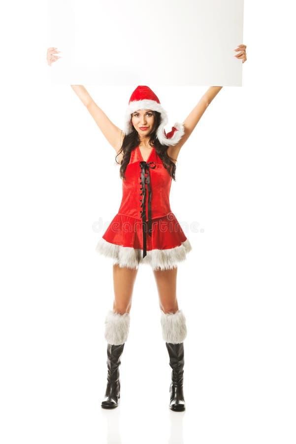 Femme de Santa tenant la bannière vide blanche vers le haut de la haute image stock