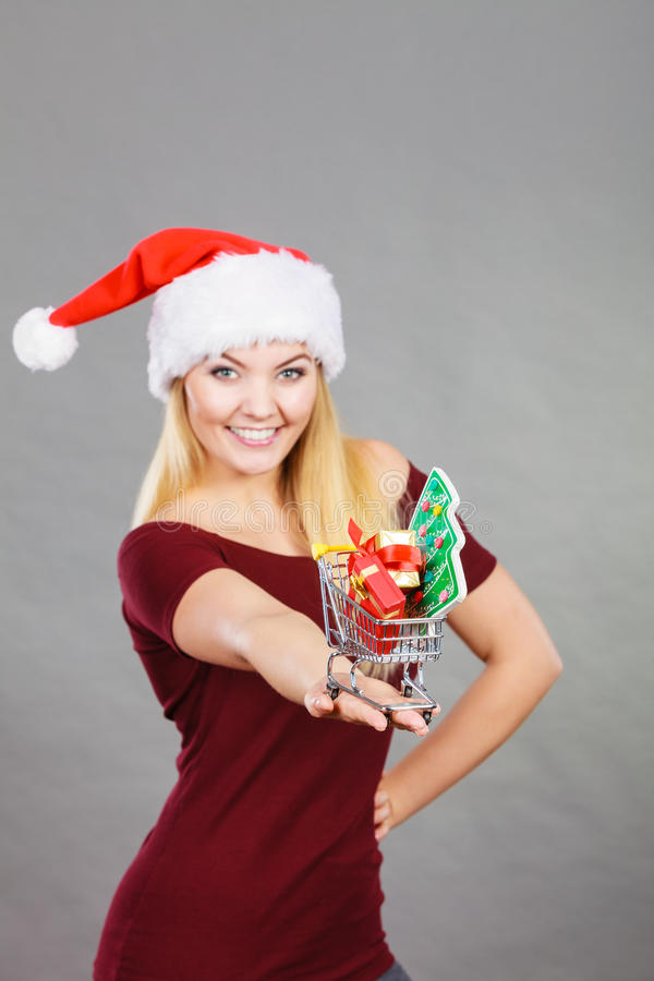 Femme de Santa tenant le caddie avec des cadeaux de Noël image stock