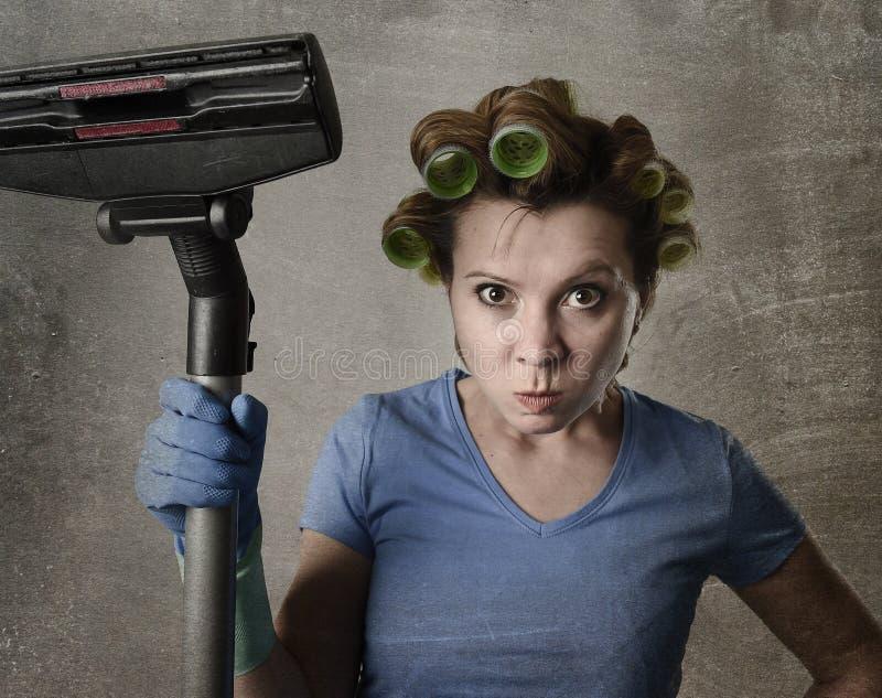 Femme de service de domestique ou femme au foyer de renversement dans des rouleaux de cheveux nettoyant des gants avec l'aspirate photographie stock libre de droits