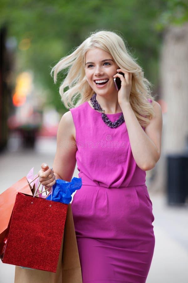 Femme de Shopaholic à un appel photographie stock libre de droits