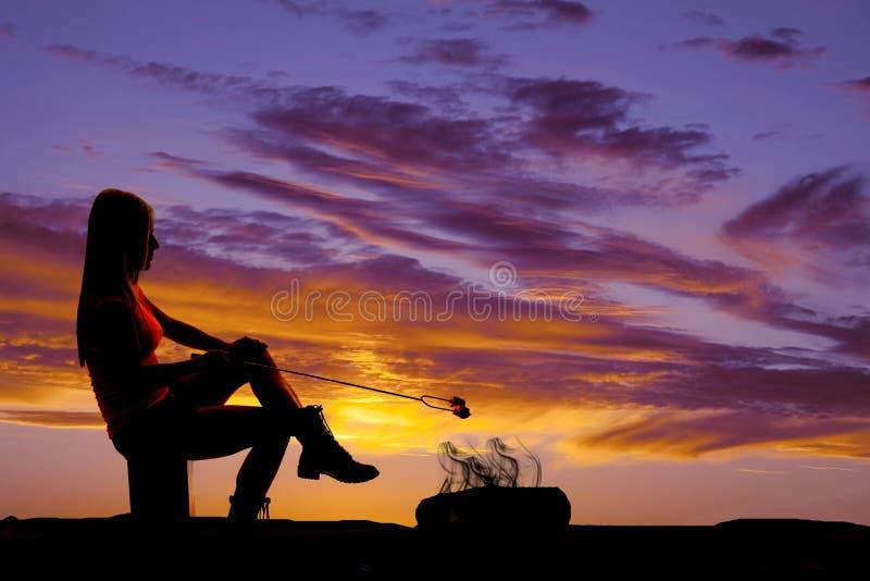 Femme de silhouette rôtissant une guimauve images stock