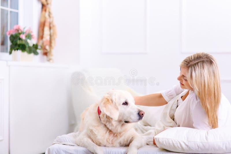 Femme de soin se trouvant sur le lit avec son chien image stock