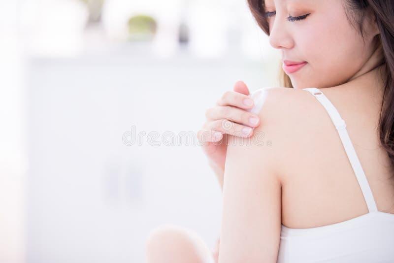 Femme de soins de la peau appliquant la lotion photo libre de droits