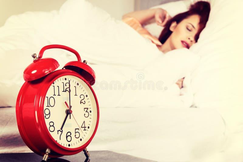 Download Femme De Sommeil Avec Son Réveil émouvant De Main Sur Le Lit Image stock - Image du matin, mensonge: 87702855