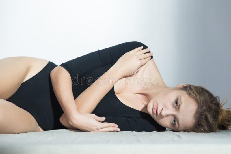 Femme de souffrance portant le corps noir photographie stock libre de droits