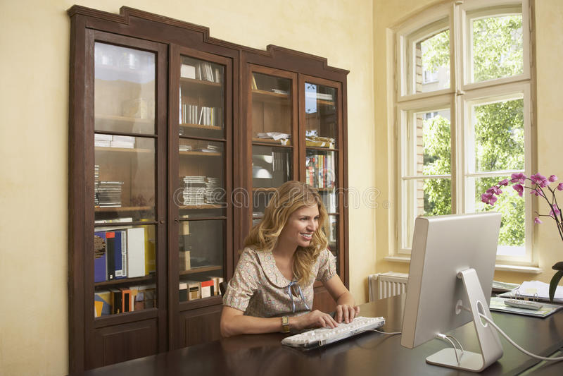 Femme de sourire à l'aide de l'ordinateur dans la chambre d'étude photographie stock