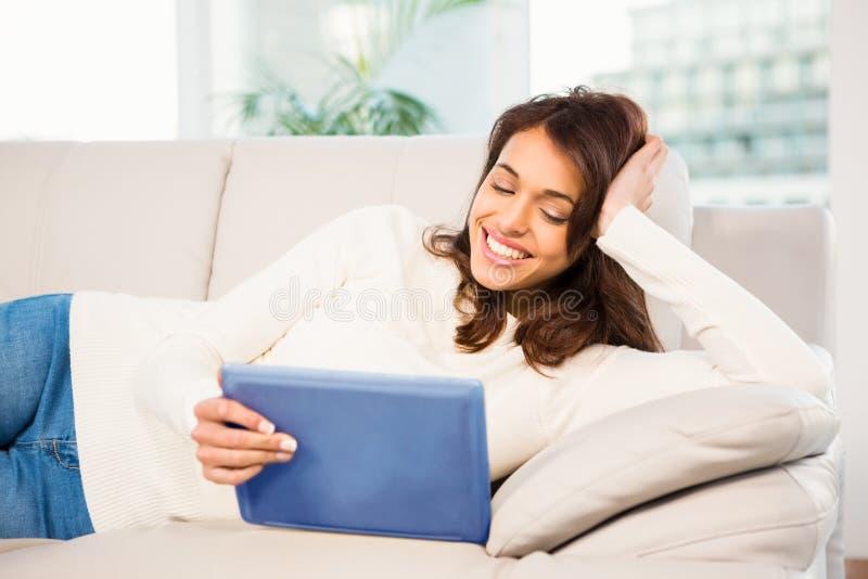 Femme de sourire à l'aide de son comprimé sur le divan photo stock