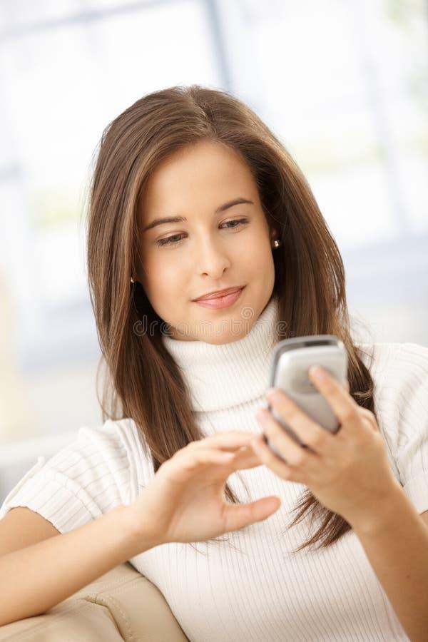 Femme de sourire à l'aide du portable image stock