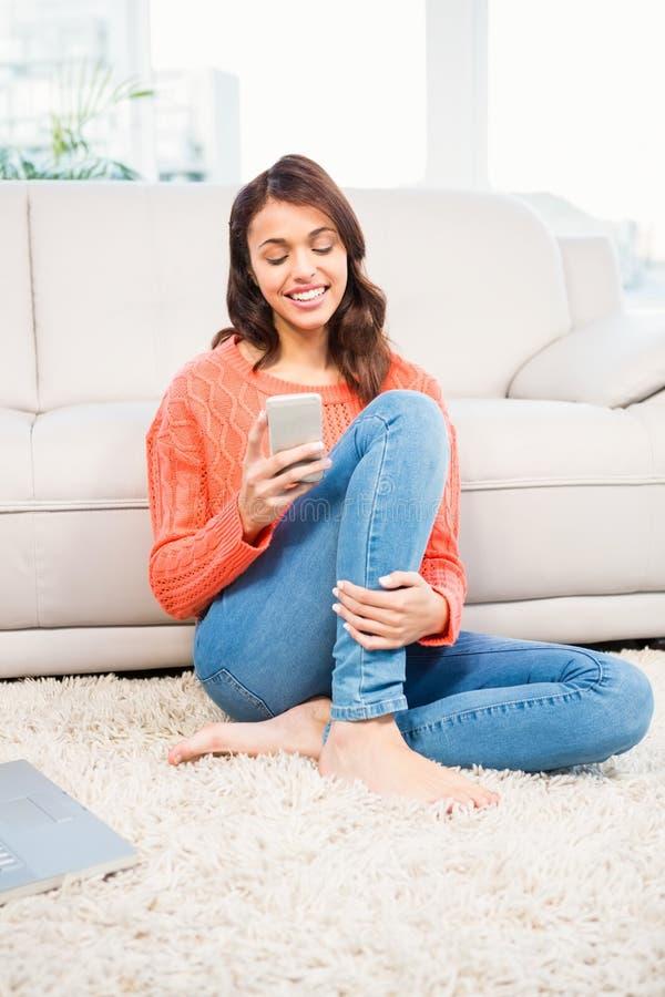 Femme de sourire à l'aide du smartphone tout en se reposant sur le plancher photographie stock