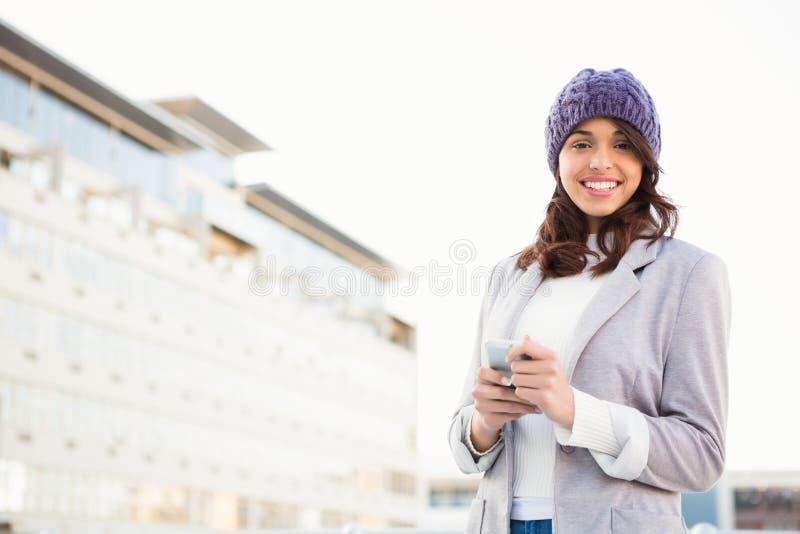 Femme de sourire à l'aide du téléphone portable photo stock
