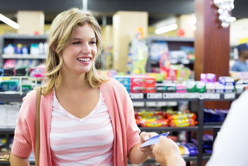 Download Femme De Sourire à La Caisse Enregistreuse Payant Avec La Carte De Crédit Image stock - Image du marché, credit: 56488101
