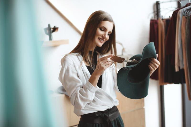 femme de sourire à la mode élégante choisissant le chapeau photos libres de droits