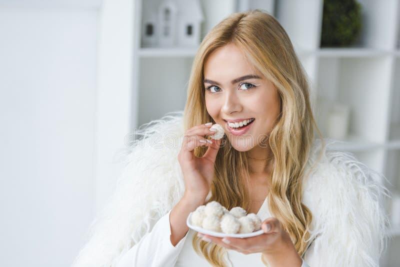 femme de sourire à la mode dans la consommation de manteau de fourrure photos stock